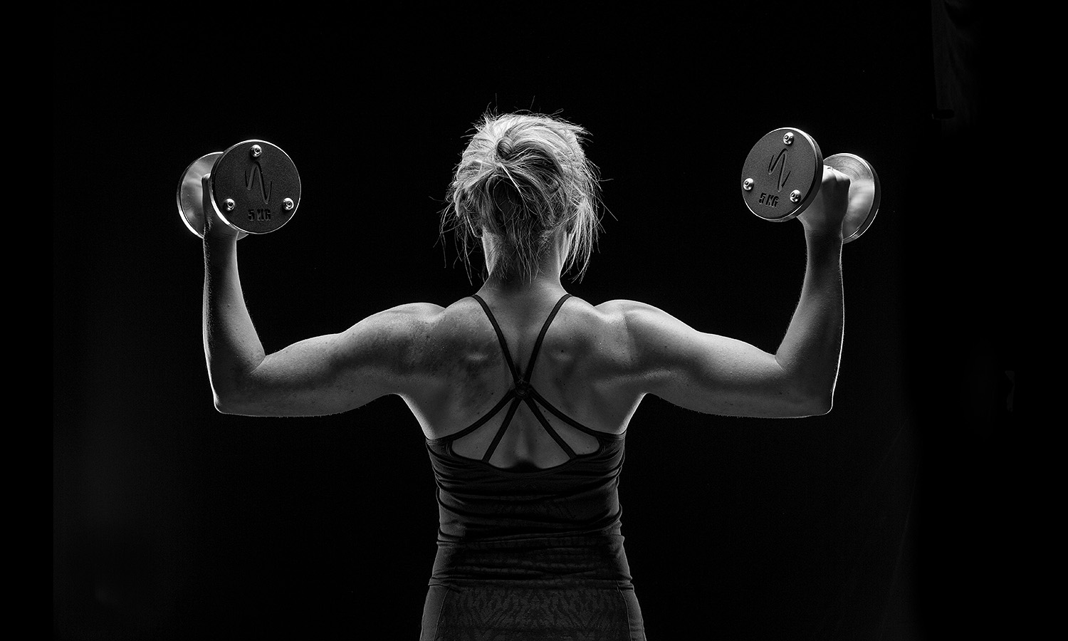 woman lifting weights detail backmuscles Fitness